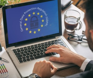 Man working with a computer, General Data Protection Regulation and European Union flag on the screen